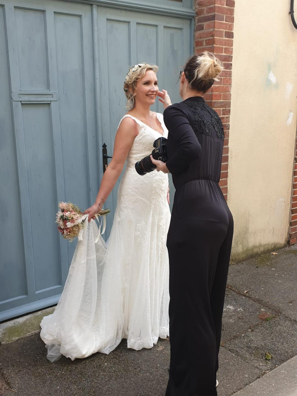 La photographe Aurélie Coquan ajuste la coiffure de sa mariée : reportage de mariage à Châteaudun